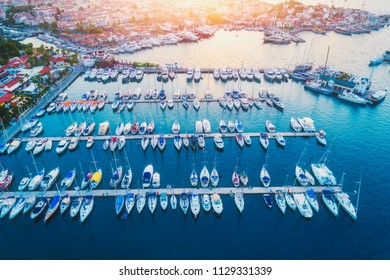 Aerial view of boats, sailboats, yachts and beautiful architecture at sunset in summer in Marmaris, Turkey. Landscape with boats in marina bay, sea, buildings in city. Top view of harbor. Travel