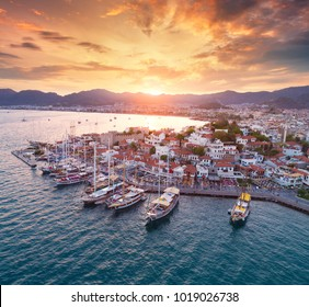 Aerial view of boats and yachts and beautiful architecture at sunset in Marmaris, Turkey. Landscape with boats in marina bay, sea, city, mountains, colorful sky. Top view from drone of harbor. Travel
