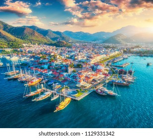 Aerial view of boats and yachts and beautiful architecture at sunset in Marmaris, Turkey. Landscape with boats in blue sea, houses, city, mountains, colorful sky with clouds. Top view of harbor