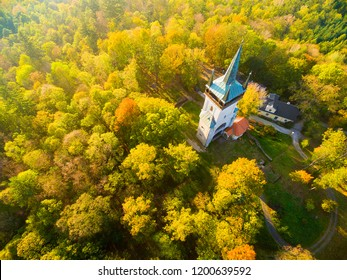 Aerial view to The Bolfanek viewtower with the St. Wolfgang´s cemetery chapel. Near a marvelous village Chudenice from 12th century. Czech landmarks from above. Golden autumn in Central Europe.