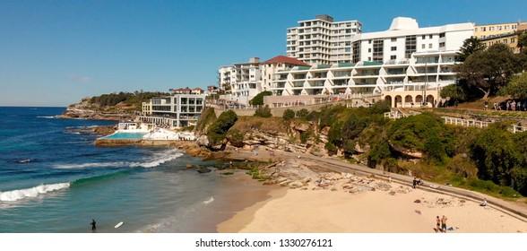 Aerial view of Bondi Beach coastline with surfers and waves, Sydney, Australia.