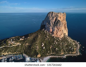 Aerial view breathtaking Penyal dIfac natural park of Penon de Ifach massive limestone on the Mediterranean sea, moored vessels on port of Calpe. Sunny day picturesque landscape. Costa Blanca, Spain
