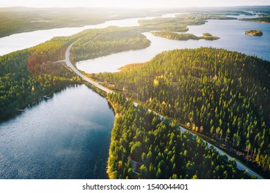 Aerial view of bridge across blue lakes with sun light in colorful autumn forest in Finland Lapland.