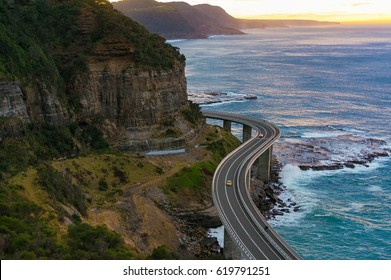Aerial view of bridge along cliff edge and ocean with traffic. Sea Cliff Bridge view on sunrise. Illawarra, New South Wales, Australia