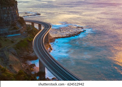 Aerial view of bridge along cliff edge and ocean. Sea Cliff Bridge view on sunrise. Illawarra, New South Wales, Australia