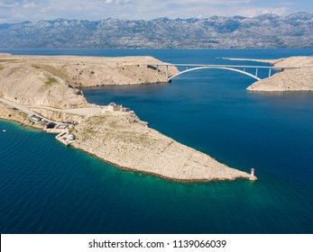 Aerial view of the bridge of the island of Pag, Croatia. Ruins of ancient Fortress Fortica on Pag Island, Croatia. Cars crossing the bridge seen from above
