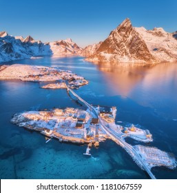 Aerial view of bridge over the sea and snowy mountains in Lofoten Islands, Norway. Reine and Hamnoy at sunrise in winter. landscape with blue water, rocks, buildings, rorbuer, road, bridge. Top view