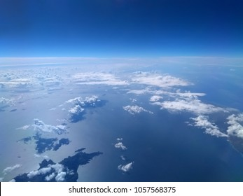 aerial view of bright blue sea and sky with white clouds casting shadows