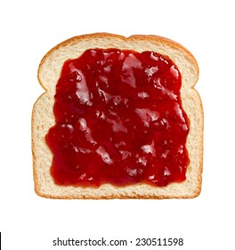 Aerial view of bright red strawberry preserves, spread over a slice of white bread.