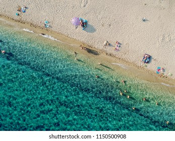 Aerial view of bright turqoise water and beach with a few people.