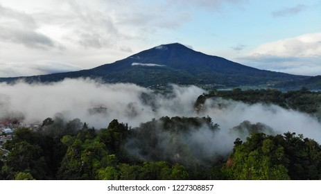 Aerial view of Bukit Tinggi Town, Padang, West Sumatera in Indonesia during hazy morning with Singgalang Mount and Merapi Mount at the background.