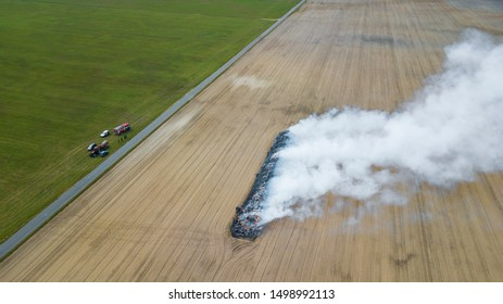 Aerial view of burnt land in the field after fire with ash and smoke