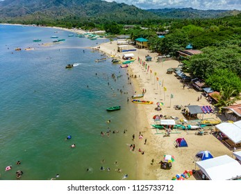 An aerial view of the busy coastline of Laiya, San Juan, Batangas with tourists enjoying the last days of summer in the Philippines