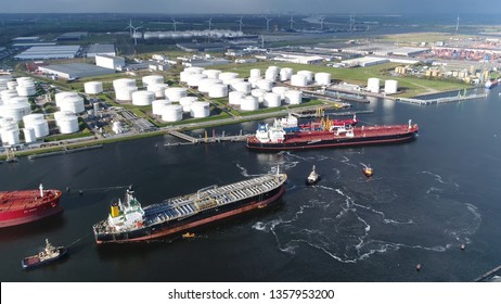 Aerial view of busy harbor area oil depot is an industrial facility for storage of petrochemical products showing tankers and tugs maneuvering the congested port waters