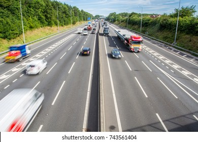 An aerial view of a busy motorway, freeway or highway with two carriageways and three lanes as well as speeding traffic in blurred motion moving through the countryside.