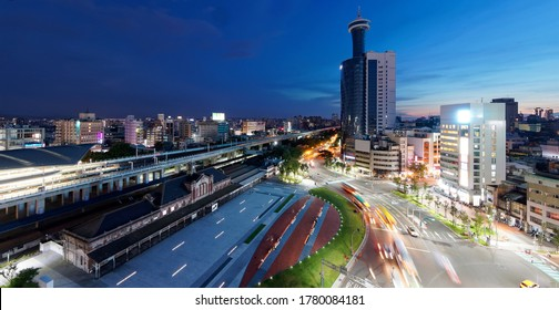 Aerial view of the busy traffic before the Old Taichung Station, a historic architecture preserved in situ & next to the new elevated railway tracks, with Le Meridien Tower under sunset sky, in Taiwan