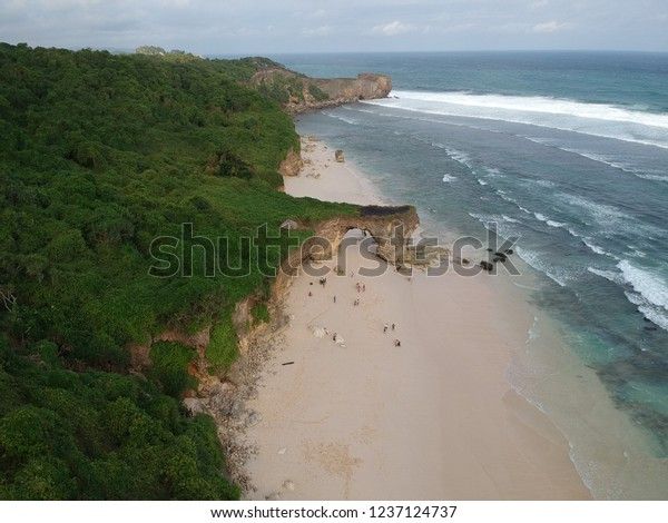 Aerial view of Bwanna beach surrounded by green hills and blue watercolor beach in Sumba island, East Nusa Tenggara Indonesia