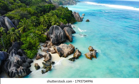 Aerial view by a drone of Anse Source d'Argent, La Digue Seychelles. Two people standing on a perfekt beach with a turquoise ocean and giant rocks in the background
