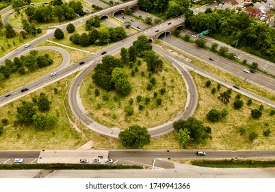 An aerial view by a New York parkway. In the center of the shot is a circular offramp. It was a cloudy day with light traffic. It was shot high enough to see the tops of the trees in the area.