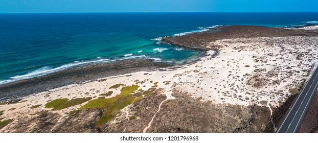 Aerial view of the Caleta del Mojón Blanco, sandy desert beach and rugged coastline. Orzola, Lanzarote, Canary Islands, Spain, Africa