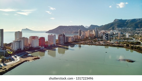 Aerial view Calpe spit between Mediterranean Sea and salt lake. Cityscape, modern skycrapers sunny day green turquoise water, comarca of Marina Alta province of Alicante, Valencian Community, Spain