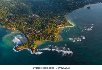 Aerial view of the cape of the town of Weligama with fisherman boats, beaches and waves breaking on the reef. Sri Lanka