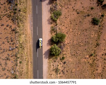 Aerial view of car driving down long dirt road, on vacation