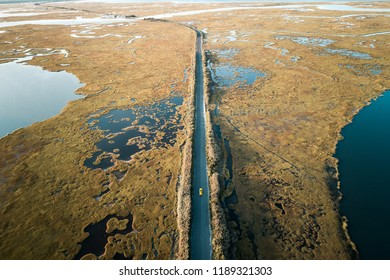Aerial view of a car driving down a road in salt marsh