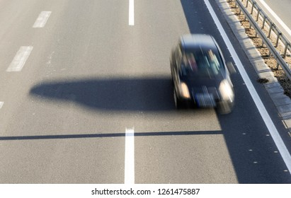 Aerial view of a car driving fast on highway with three lanes and road fence barrier