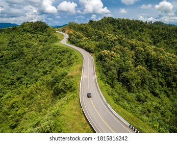 Aerial view of car driving on beautiful steep curved road (look like number 3) on the high mountain in Nan province, Thailand.