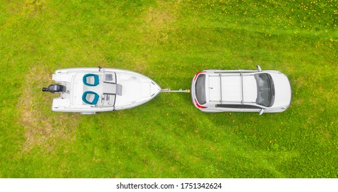 Aerial view car with a white fishing motor boat at the trailer at the green grass. Top aerial view car with fishing boat on trailer