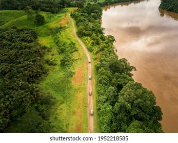 Aerial view caravan of cars next to a river