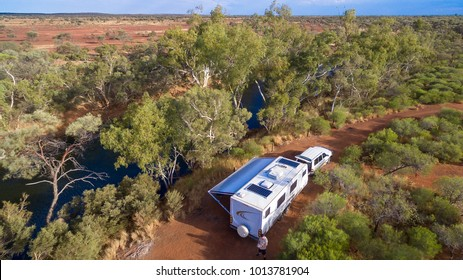 Aerial view of caravan and four wheel drive vehicle camped next to a river pool in the outback of Australia