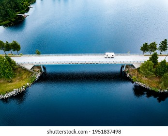 Aerial view Caravan trailer or Camper rv on the bridge over the lake in Finland. Summer holiday trip.