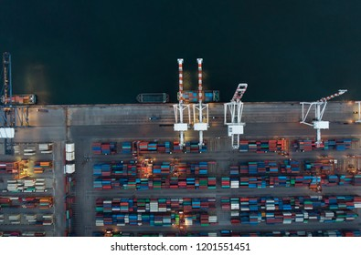 Aerial view of cargo container ship in the cargo international yard port at night.