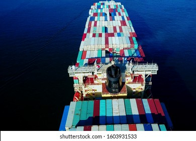 Aerial view of a cargo ship sailing with hundreds of colored containers