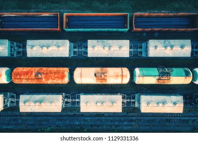 Aerial view of cargo trains. Railway wagons with goods on railroad. Top view of colorful freight train on the railway station. Heavy industry. Industrial conceptual landscape. Transportation. Vintage