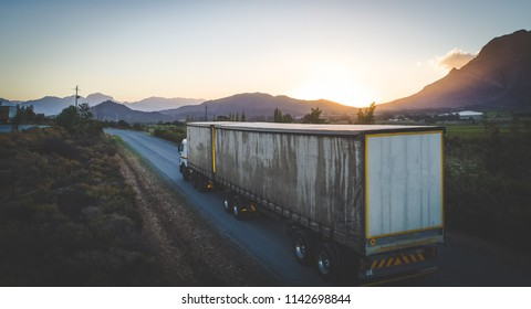 Aerial view of a cargo truck driving of into the sunset