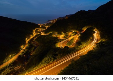 Aerial view of cars driving on curved, zigzag road or street on mountain hill with natural forest trees in rural area of New Taipei City, Taiwan at night