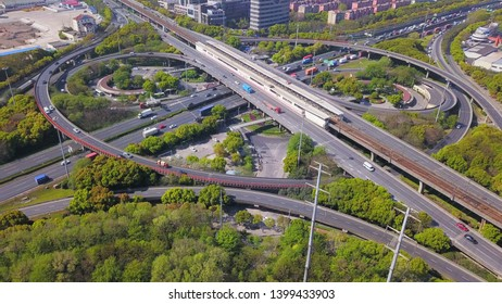 Aerial view of cars on highway junctions with roundabout. Bridge roads shape circle in structure of architecture and transportation concept. Top view. Urban city, Shanghai, China.