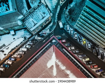 An aerial view of cars parked diagonally in a city street during winter