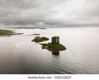Aerial view of Castle Stalker in Loch Linnhe during a rainy autumn day with moody sky (Castle Stalker, Scotland, United Kingdom, Europe)