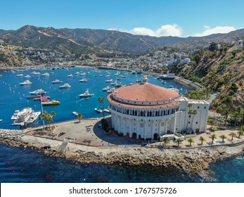 Aerial view of Catalina Casino and Avalon harbor with sailboats, fishing boats and yachts moored in calm bay, famous tourist attraction in Santa Catalina Island, Southern California. June 20th, 2020