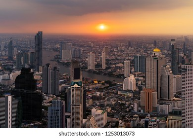 Aerial view of Chao Phraya River with the sun, Bangkok Downtown. Financial district and business centers in smart urban city in Asia. Skyscraper and high-rise buildings at sunset.