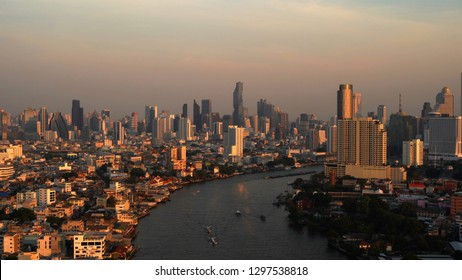 Aerial view of Chao Phraya River, Bangkok Downtown. Thailand. Financial district and business centers in smart urban city in Asia. Skyscraper and high-rise buildings at sunset.