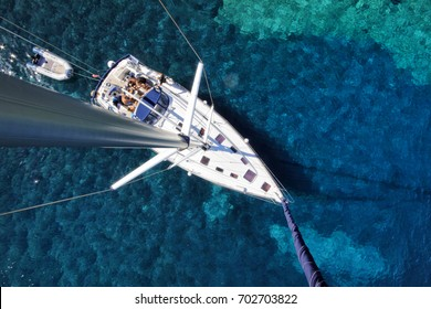 Aerial view of a charter sailboat yacht sailing in emerald and turquoise sea near islands in Croatia