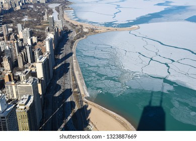 aerial view of Chicago city buildings shadows on Lake Michigan shoreline in winter