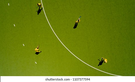 Aerial view of children playing hockey on the grass. Top view.