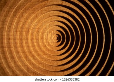 Aerial view of a circular geometric vertical beech wood plate. Concentric round beech wood plate light and shadow.