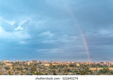 Aerial view of the city of Addis Ababa covered by a rainbow and dark clouds
